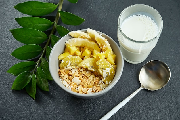 Close up view on healthy breakfast: granola with coconut, mango, bananas and yellow kiwi in a blue bowl served with milk on a black surface.