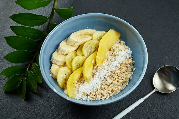 Close up view on healthy breakfast: oatmeal with coconut, mango, bananas and yellow kiwi in a blue bowl on a black surface