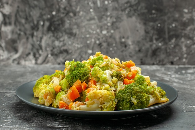 Close up view of healthy meal with brocoli and carrots on a black plate with fork and knife