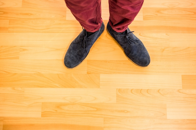 Close up view of hipster shoes against overhead of wooden planks