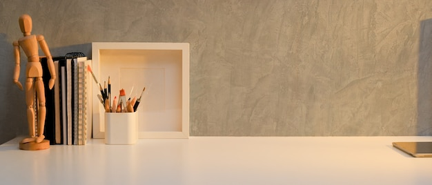 Close up view of home office desk with mock up frame, stationery, copy space and decoration