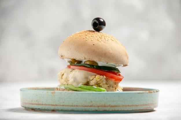 Vista ravvicinata di un delizioso panino fatto in casa con oliva nera su un piatto su una superficie bianca macchiata con spazio libero