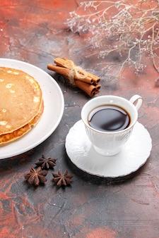 Vista ravvicinata di frittelle fatte in casa e cannella lime una tazza di tè sul colore misto