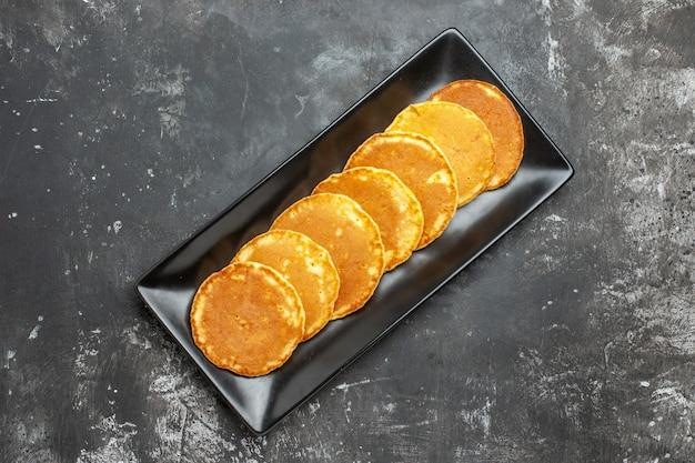 Vista ravvicinata di frittelle fatte in casa allineate su un piatto nero a forma quadrata su grigio