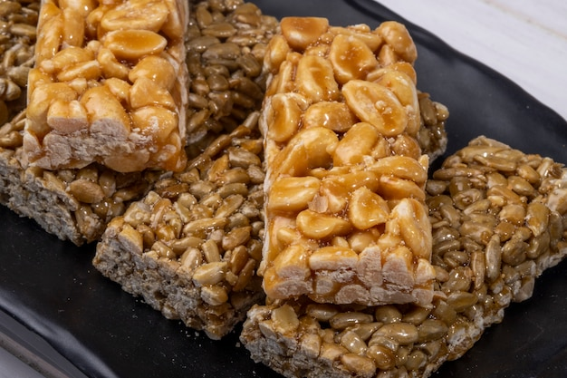 Close up view of honey bars with peanuts and sunflower seeds on black