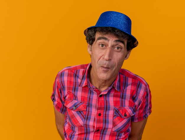Close-up view of impressed middle-aged party man wearing party hat looking at front keeping hands behind back isolated on orange wall with copy space
