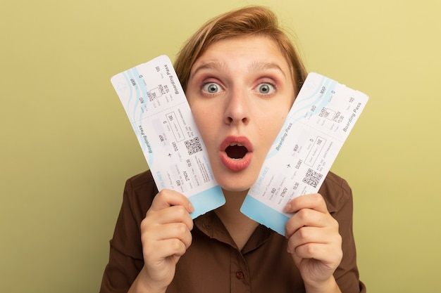Close-up view of impressed young blonde girl holding airplane tickets touching face with them  isolated on olive green wall