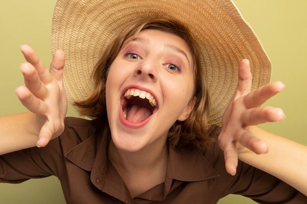 Vista ravvicinata di una giovane ragazza bionda impressionata che indossa un cappello da spiaggia che tiene le mani in aria isolate su un muro verde oliva