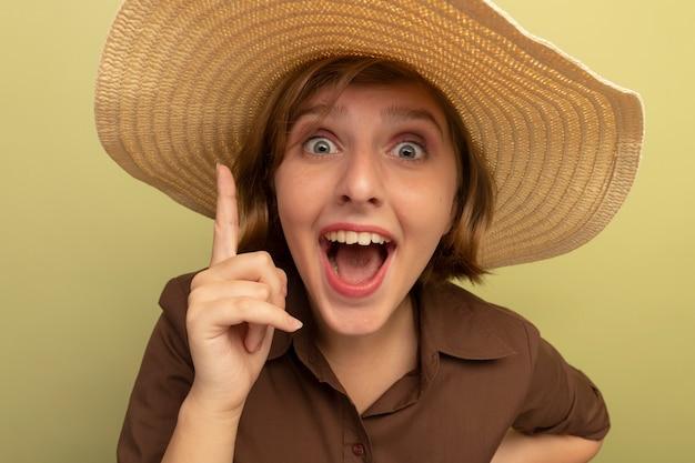 Vista ravvicinata di una giovane ragazza bionda impressionata che indossa un cappello da spiaggia rivolto verso l'alto