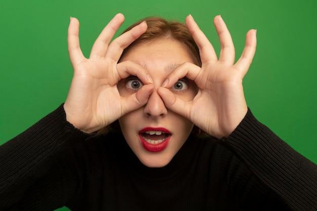 Vista ravvicinata della giovane donna bionda impressionata che guarda davanti facendo un gesto di sguardo usando le mani come binocolo isolato sul muro verde green
