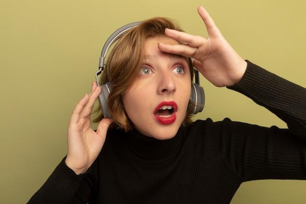 Vista ravvicinata della giovane donna bionda impressionata che indossa e tocca le cuffie tenendo la mano sulla fronte guardando il lato in lontananza isolata sul muro verde oliva