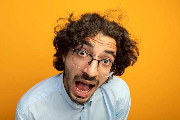 Vista ravvicinata del giovane uomo bello colpito con gli occhiali guardando la parte anteriore isolata sulla parete arancione