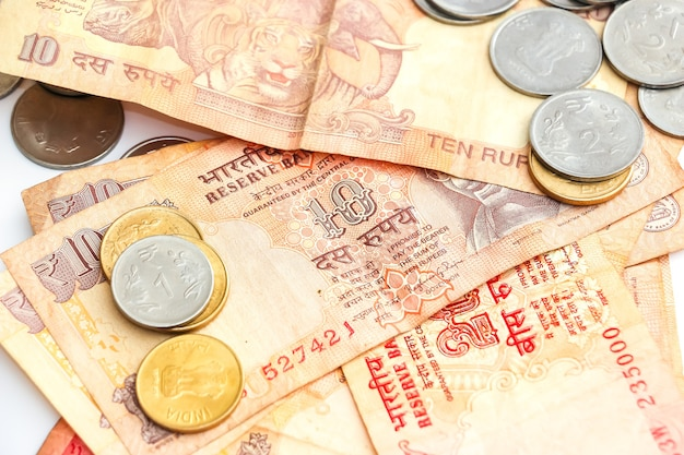 Close up view of indian banknotes and coins on white background.