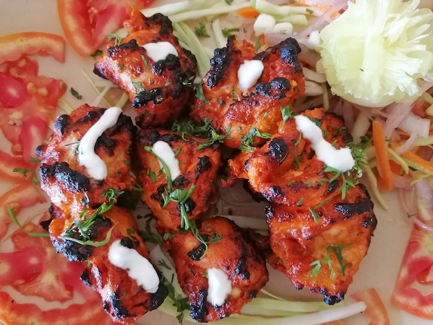 Close-up view of an indian dish chicken tikka tandoori, laid out on rings of tomatoes and garnished with salad