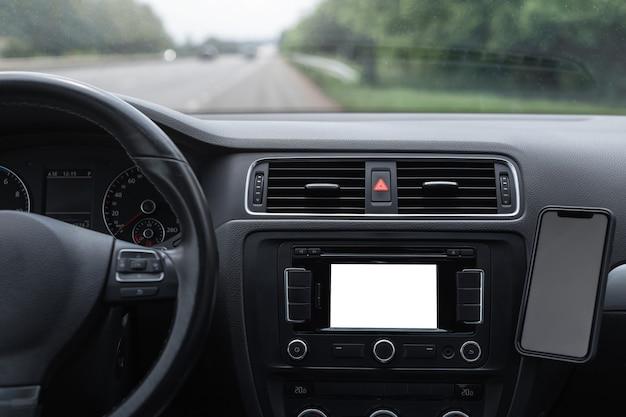 Крупным планом вид приборной панели внутри автомобиля с пустым макетом на экране и смартфона