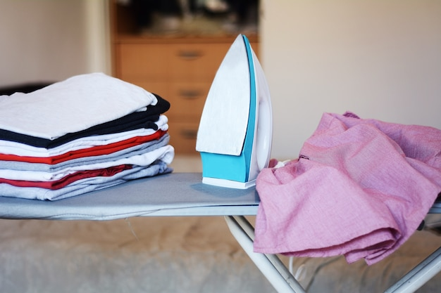 Close up view of iron clothes on ironing board with stack of ironed shirts