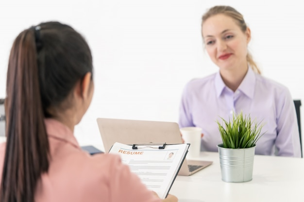 Close up view of job interview focusing on woman handing resume with the office