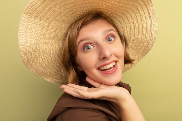 Vista ravvicinata della gioiosa giovane ragazza bionda che indossa un cappello da spiaggia in piedi nella vista di profilo guardando il mento commovente isolato sul muro verde oliva