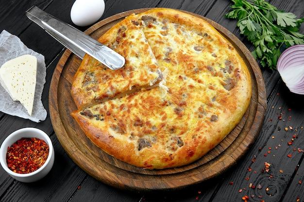 スパイスと暗い背景のビューkhachapuriを閉じます。伝統的な。白人のキッチン。レストランの料理。ハチャプリパイとチーズと細切りのベフ。ランチの肉料理、暗い背景。コピースペース Premium写真