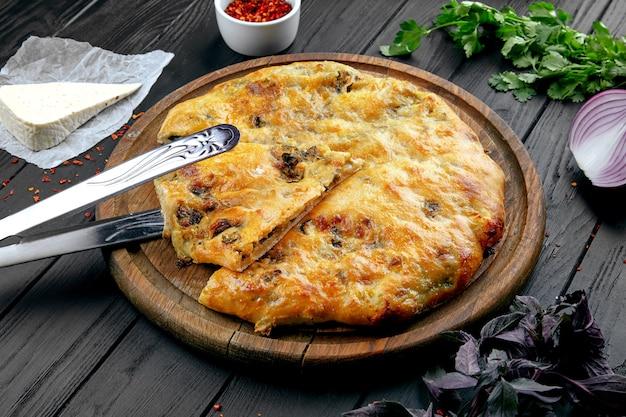 スパイスと暗い背景のビューkhachapuriを閉じます。伝統的な。白人のキッチン。レストランの料理。ハチャプリパイとチーズと細切りのベフ。ランチの肉料理、暗い背景。コピースペース
