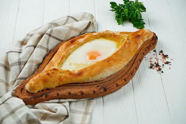 スパイスと白い背景の上のビューkhachapuriを閉じます。伝統的なグルジア料理のチーズ入りパン。アジャリアンのカチャプリ。チーズと卵のパイを開く