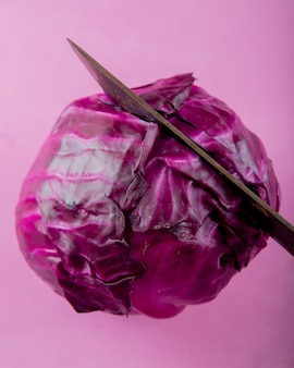 Close-up view of knife cutting purple cabbage on purple background