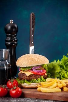 Vista ravvicinata del coltello in sandwich di carne e pomodori fritti con gambo verde fascio su tavola di legno salsa ketchup su superficie blu scuro