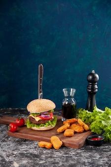 Vista ravvicinata del coltello in gustoso sandwich di carne e pepite di pollo pomodori con gambo pepe su tavola di legno salsa ketchup su superficie blu scuro
