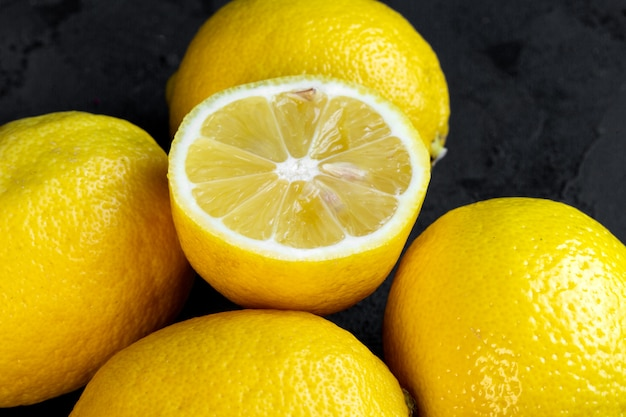 Close up view of lemons and a half on black
