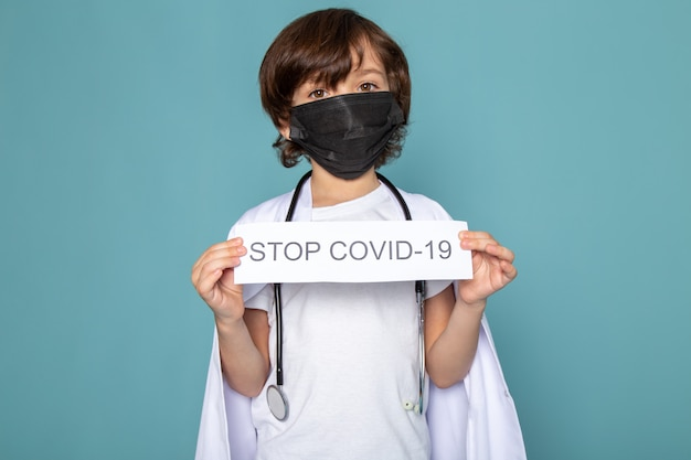 Close up, view little child boy adorable in black sterile protective mask holding stop covid written paper on blue desk