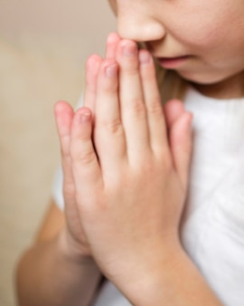Close-up view of little girl praying