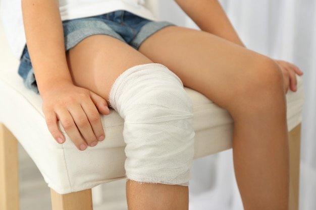 Close up view of little girl's knee with bandage