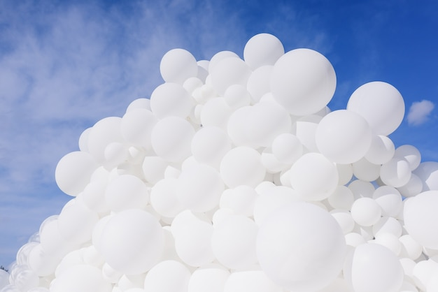 Close up view of a lot of white balloons on the sky background