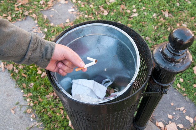 Close up view of male hand throwing broken cigarette in trash can.