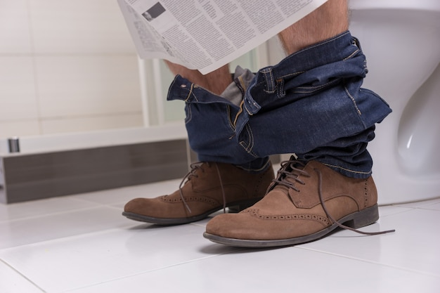 Close up view of male wearing jeans and shoes reading newspaper while sitting on the toilet seat in  the modern tiled bathroom at home