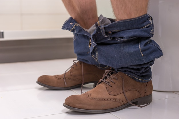 Close up view of male wearing jeans and shoes sitting on the toilet seat in  the modern tiled bathroom at home