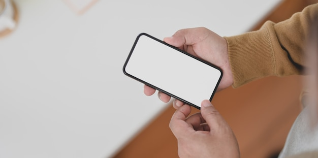 Close-up view of man hands holding blank screen smartphone