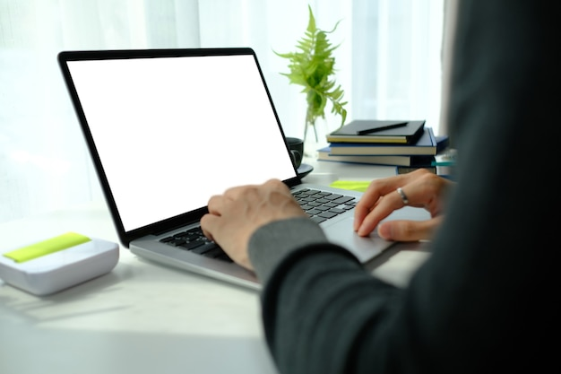 Close up view of man hands typing on laptop computer while sitting at comfortable home office.