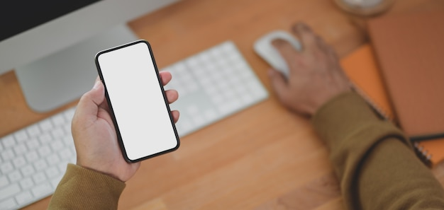 Close-up view of man holding blank screen smartphone while working on his project