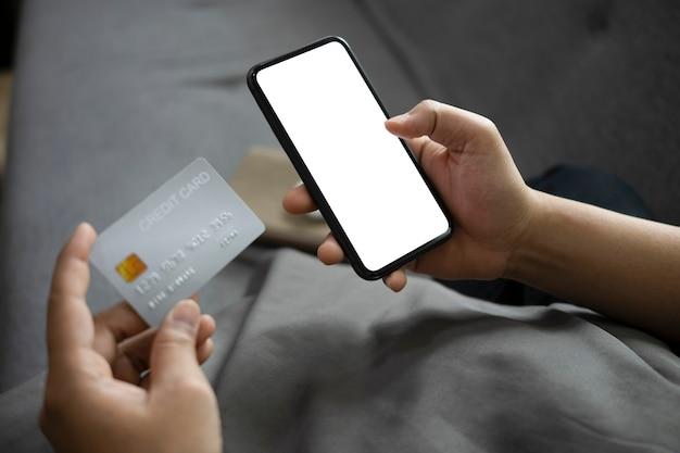 흰색 화면과 신용 카드가 있는 스마트 폰을 들고 있는 보기 남자를 닫습니다.