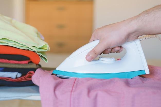 Close up view of man ironing blue shirt on ironing board