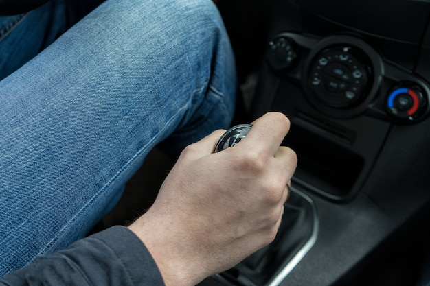 Close-up view of man's hand changing gear while driving car