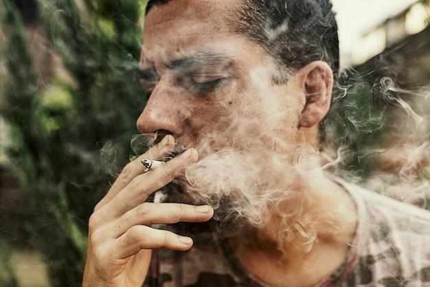 Close up view of man smoking marijuana cigarette outdoors