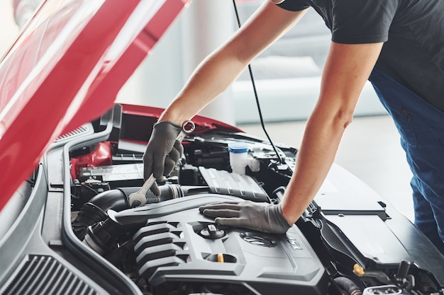 Close up view of man in uniform that works with broken automobile. conception of car service