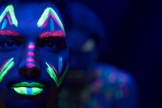 Close-up view of man with fluorescent make-up