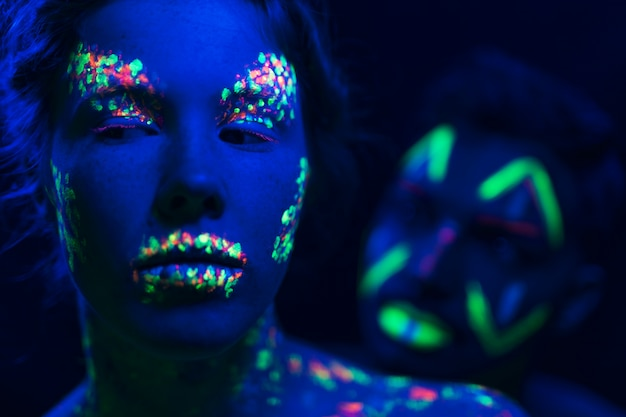 Close-up view of man and woman with fluorescent make-up