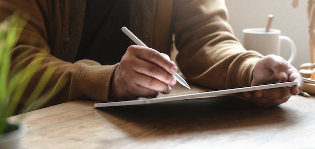 Close-up view of man working on his project while using tablet in his comfortable office