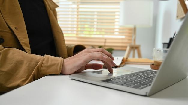 Крупным планом вид человека, работающего онлайн с портативным компьютером у себя дома.