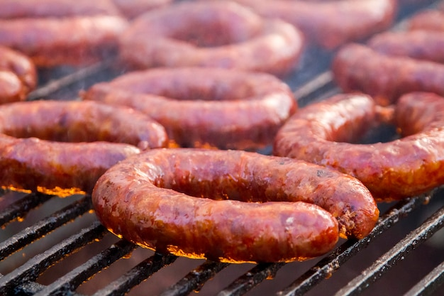 Close up view of many portuguese chorizos on a barbecue.