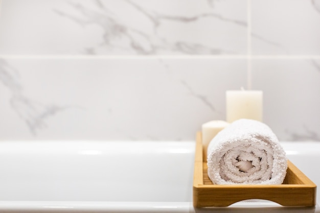 Close up view of marble white bathroom accessories, white towels, candles and copy space side view